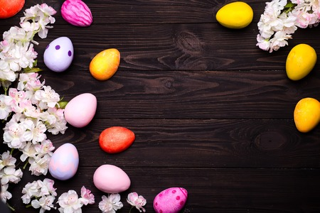 frame of cherry-tree flowers and easter eggs isolated on dark wooden background, flat lay copy space Stock Photo