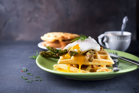 hams: egg benedict and asparagus, with waffles and coffee on a dark stone background