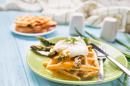 egg benedict and asparagus, with waffles and coffee on a blue wooden background