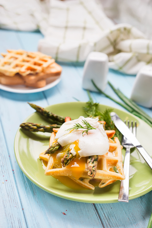 benedict: egg benedict and asparagus, with waffles and coffee on a blue wooden background
