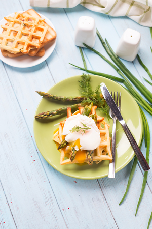 Healthy breakfast served on green plate on a blue wooden background