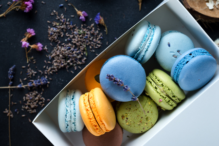 rotates: Different colorful macaroons in gift box on black stone background, flat lay Stock Photo