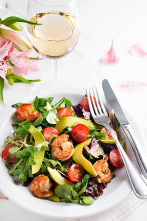 Avocado shrimp salad with cherry tomatoes with a glass of white wine and flowers on a light background