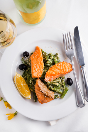 Baked Wild Alaskan Salmon Served with Green Beans and lemon with wine on a light background Stock Photo