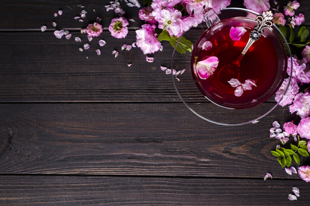 Floral frame consists of pink flowers with tea cup on wooden background. Top view. Flat design. Copy space.