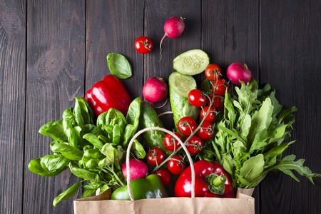Paper bag of different health vegetables on a black wooden background. Top view. Flat lay Stock Photo