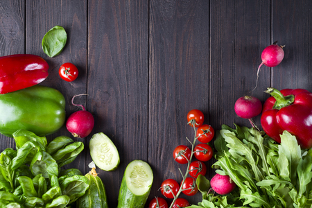 frame of different health vegetables on a black wooden background. Top view. Flat lay Stock Photo