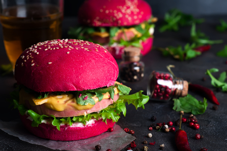 Burgers with red bun and greens on a black background Stock Photo