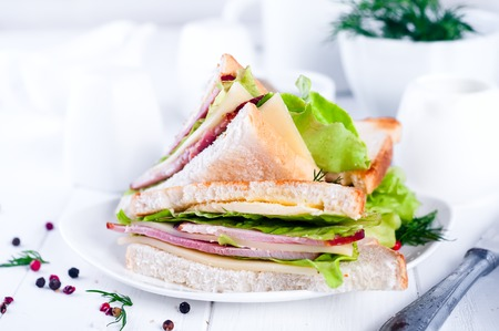 A view of breakfast table. Healthy Sandwich toast with lettuce, ham, cheese, salami and tomato on a wooden background