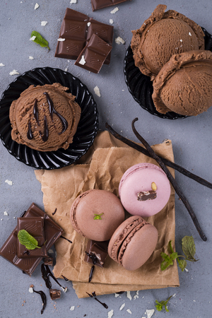 rotates: Chocolate macaroons with ice cream mint leaves and chunks of chocolate flat lay Stock Photo