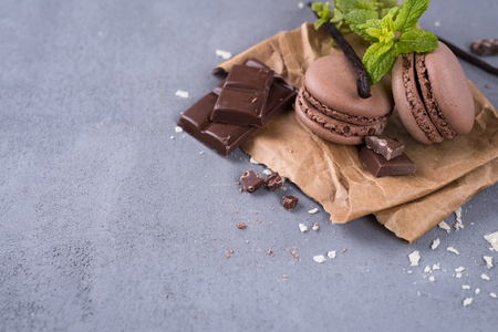 rotates: Chocolate macaroons with pieces of black chocolate on stone table