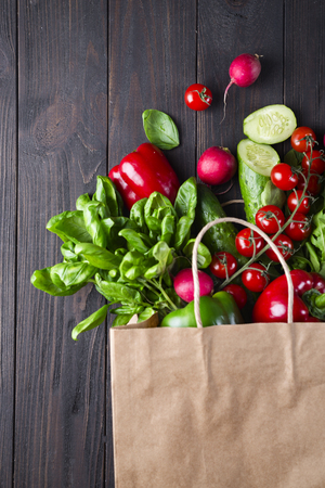Fresh healthy groceries in a paper bag on a black wooden background. Top view. Flat lay