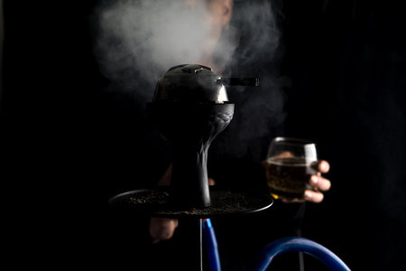 Man smokes hookah. Hookah bowl with tobacco and smoke on black background Stock Photo