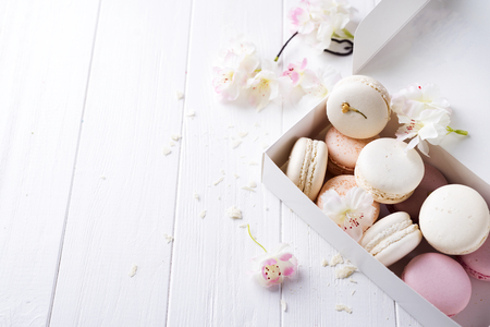 Macaroons colored cake in a gift box with a flowers. French dessert on a white background .With space under the text Stock Photo