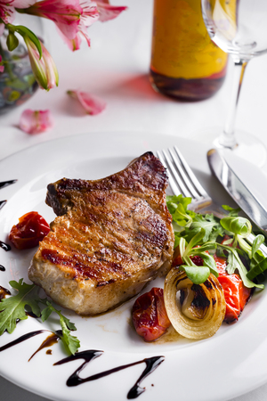 Thick juicy portions of roast fillet steak served with vegetables in a plate