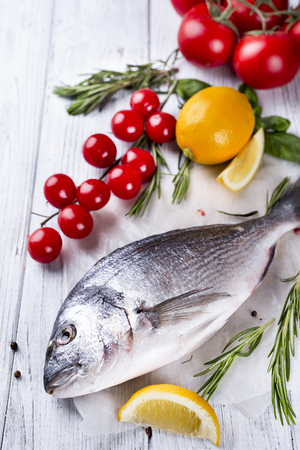 Fresh raw sea fish, decorated with lemon slices, herbs and tomatoes on a white wood background. Concept of healthy eating, top view,