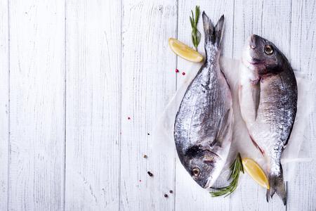 Roher frischer Dorado Fisch mit Zitronenrosmarin und Gewürzen. Gesundes Essen flach legen Standard-Bild - 77930322