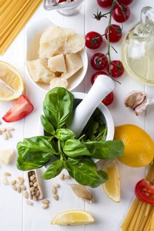 Italian food concept .Various kind of pasta with ingredients sweet basil ,tomato ,garlic ,parsley ,bay leaves ,pepper , and parmesan cheese on white wooden background flat lay. Stock Photo