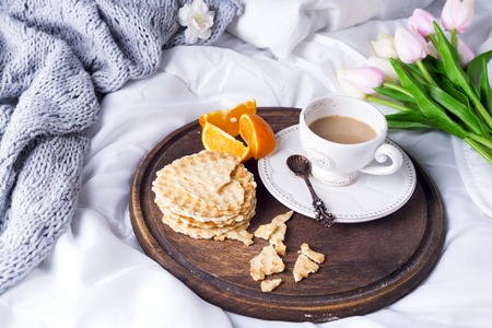 living room design: wooden tray with a cup of coffee with milk, waffles and oranges on a white pastel with tulips and a knitted plaid, copy space flat lay