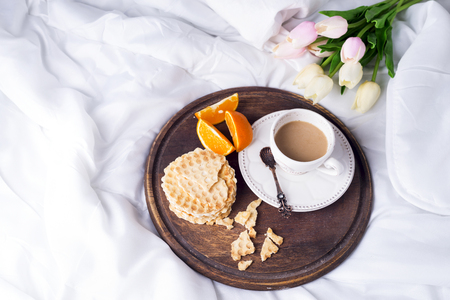 living room design: wooden tray with a cup of coffee with milk, waffles and oranges on a white pastel with tulips , copy space flat lay Stock Photo
