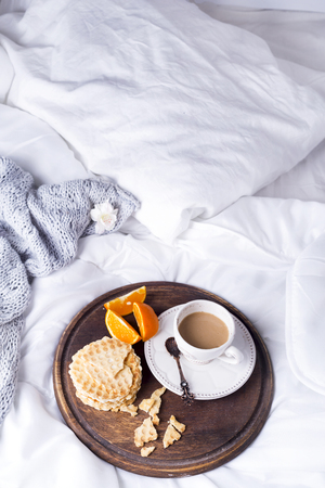 living room design: A cup of hot coffee with milk on a tray with orange and waffles on a snow-white pastel with a knitted plaid, copy space flat lay