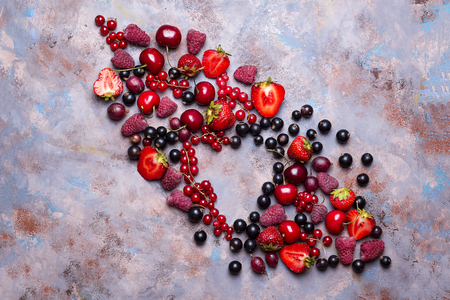 Fresh juicy berries in the form of a heart with a place under the text on a stone background Stock Photo