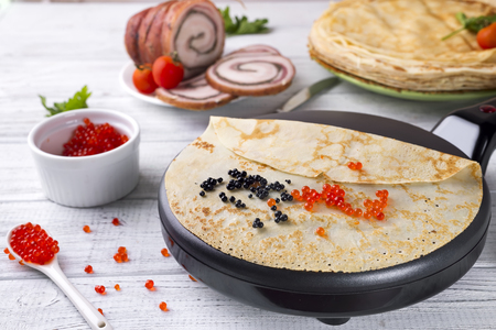 Pancakes in a frying pan with Salmon Caviar Stock Photo