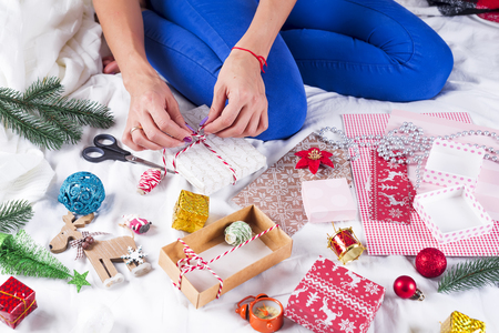 Girl in a cozy knit sweater decorated with a Christmas gift box