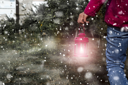Woman hand with latern. Christmas background with snow in outdoor Stock Photo