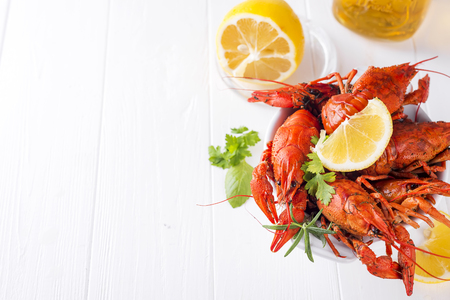 Boiled crayfish in the plate with beer, lemon and spices on white background copy space flat lay Imagens