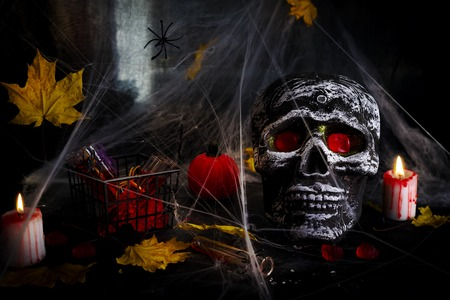 Happy Halloween Party Table with spider web, skull and candy and burning candles against spider web background.