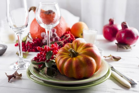 Thanksgiving autumn place setting with cutlery and arrangement of colorful fall leave