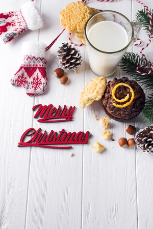 Freshly baked homemade chocolate muffins with jug with milk on the white wooden table for Santa Claus, Christmas concept, copy space flat lay Stock Photo