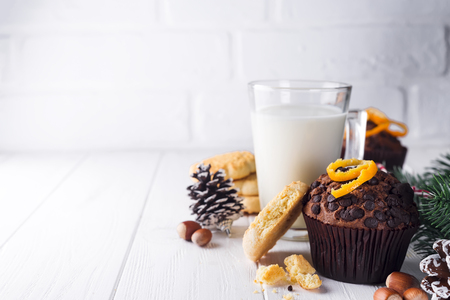 Freshly baked homemade chocolate muffins with jug with milk on the white wooden table, Christmas concept, copy space