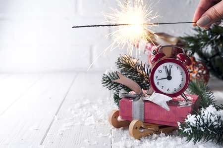 New Years clock. Christmas decorations, gift box and sleigh with burning Bengal fire on white wooden background . Christmas background or greeting card. Copy space