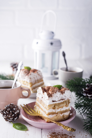 Traditional italian dessert tiramisu on plate with christmas decoration on white background Stock Photo