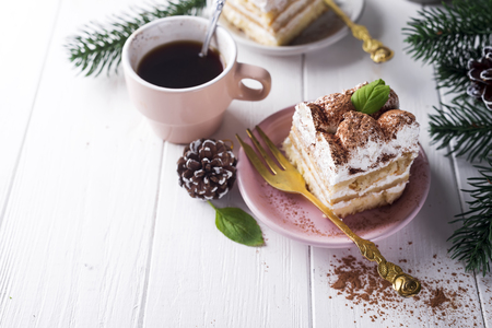 Traditional italian dessert tiramisu on plate with christmas decoration on white background, copy space