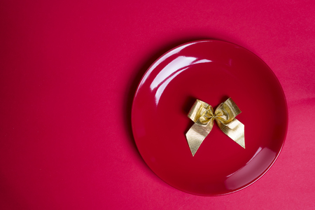 Gold ribbon on red plate isolated on red, flat lay copy space. Valentines concept