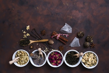 Collection of tea and natural additives in bowls on old wooden table, flat lay copy space