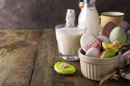 Plate with colourful Easter cookies and glass of milk, rustic style Stock Photo