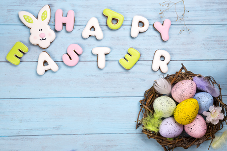 colorful eggs in nest on blue wooden background and cookies lettering Happy Easter Banque d'images