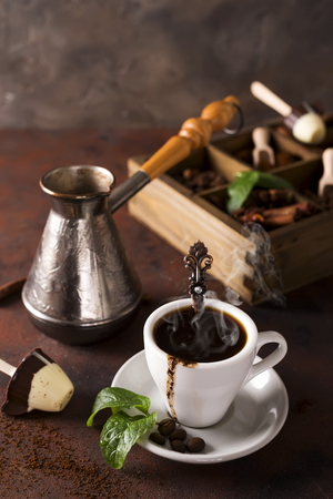 Cup of coffee with cooffee beans and mint leaves, wooden box with grains of coffee and spices, cezve on a stone background