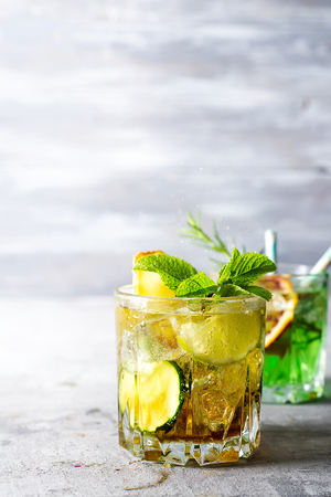 Refreshing cold alcoholic summer citrus cocktail with orange, peppermint and cucumber ice in stemless glasses