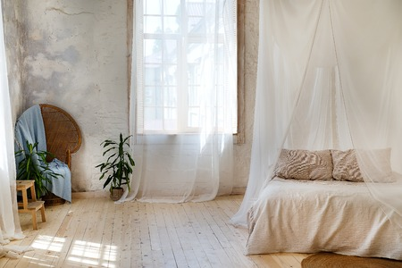 a cozy bedroom in pastel colors with a wooden floor, a large four-poster bed, a green flower in a flowerpot, a wicker chair and a large window Archivio Fotografico
