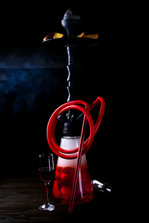 Stylish oriental shisha with fruits on a black background. Archivio Fotografico