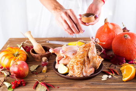 The woman's hands sprinkle with salt a whole raw chicken in a plate with an apple, orange and spices on a wooden table. Step by step cooking.