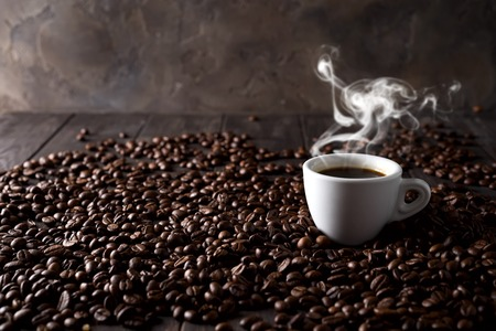 cup of hot coffee on the background of coffee grains on a dark wooden background, place under the text