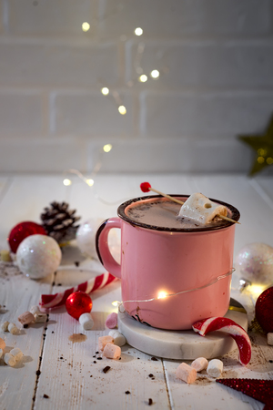 Enamel cup of hot cocoa with mini marshmallows and candy canes with beautiful Christmas lights of bokeh. Christmas concept Stock Photo