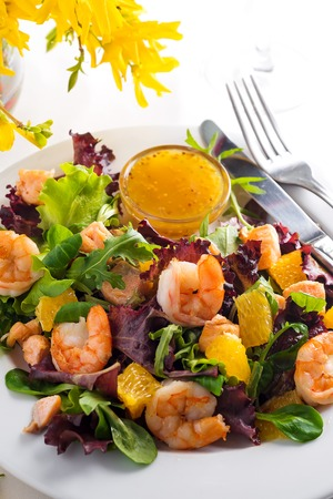 Healthy salad with prawns, lettuce, oranges and mango served on a plate with orange mustard sauce, close up