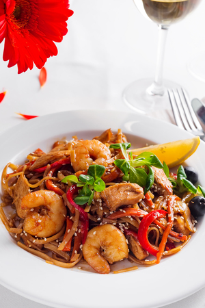 Rice noodles with shrimps in sauce on a white plate, close up